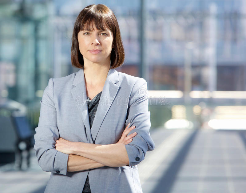 Ernste Geschäftsfrau in der grauen Klage, die in der Stadt steht lizenzfreies stockfoto