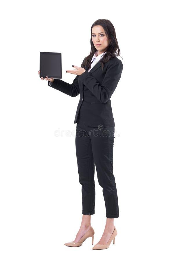 Ernste Geschäftsfrau in der schwarzen Anzugs- oder Verkäuferinmarketing-Schwarztabletten- oder -auflagenanzeige lizenzfreie stockfotografie