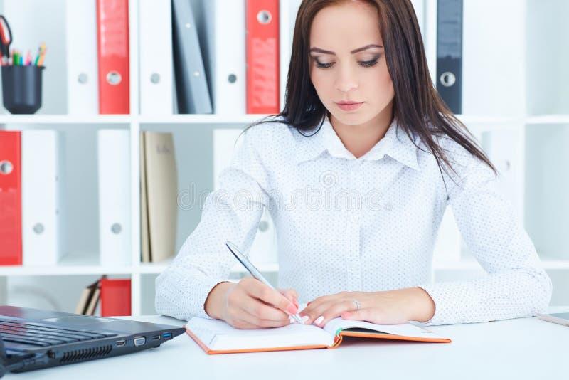 Ernste Geschäftsfrau, die Anmerkungen am Büroarbeitsplatz macht Angebot der kommerziellen Aufgabe, Finanzerfolg, zugelassene Öffe lizenzfreie stockfotos