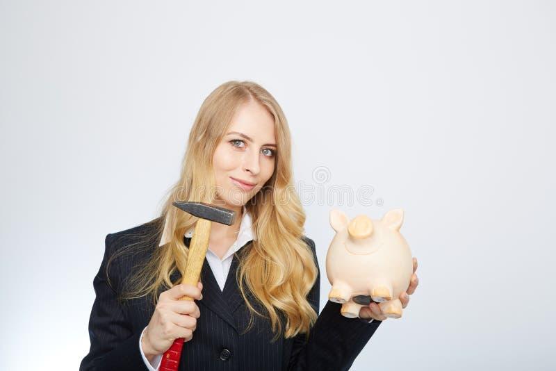 Ernste Geschäftsfrau, die ein Sparschwein hält und stockfoto