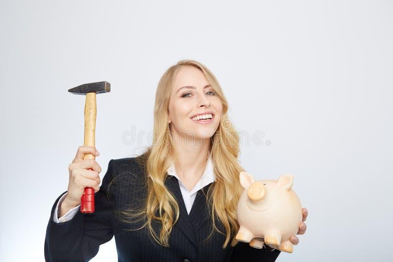 Ernste Geschäftsfrau, die ein Sparschwein hält und stockbilder