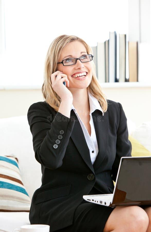 Ernste Geschäftsfrau, die Laptop anruft und verwendet stockfotos