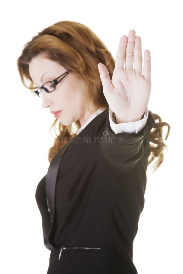 Ernste Geschäftsfrau, die Stoppschild gestikuliert lizenzfreies stockbild