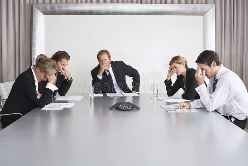 Ernste Geschäftsleute auf Telefonkonferenz lizenzfreie stockbilder