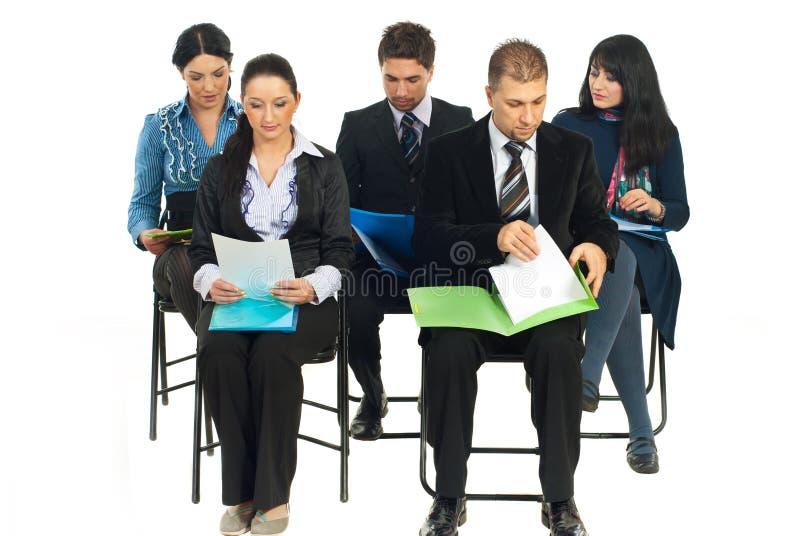 Ernste Geschäftsleute, die bei der Konferenz lesen stockbild