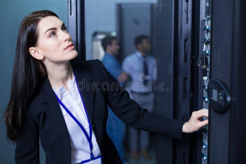 Ernste intelligente Frau, die mit informierender Technologie arbeitet stockbild