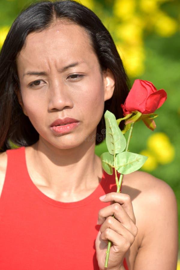 Ernste jugendliche erwachsene Frau mit einer Rose stockfotos
