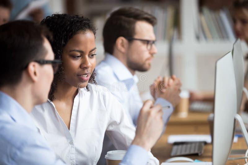 Ernste junge Afroamerikanerfrau, die mit Kollegen spricht lizenzfreies stockbild