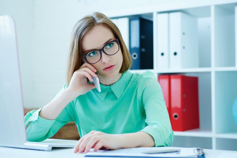 Ernste junge attraktive Geschäftsfrau in den Gläsern, die am Bürostuhl arbeitet am Tischrechner sprechend auf Mobile sitzen lizenzfreies stockbild