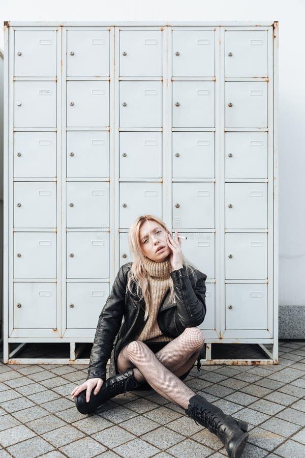 Ernste junge blonde Dame, die nahe Safes sitzt lizenzfreie stockfotografie