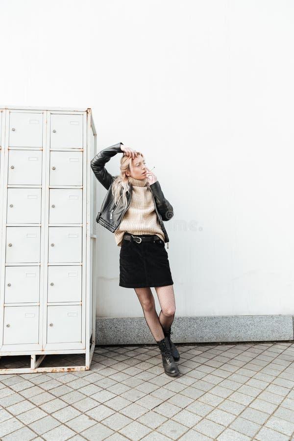 Ernste junge blonde Dame, die nahe Safes steht stockfotografie