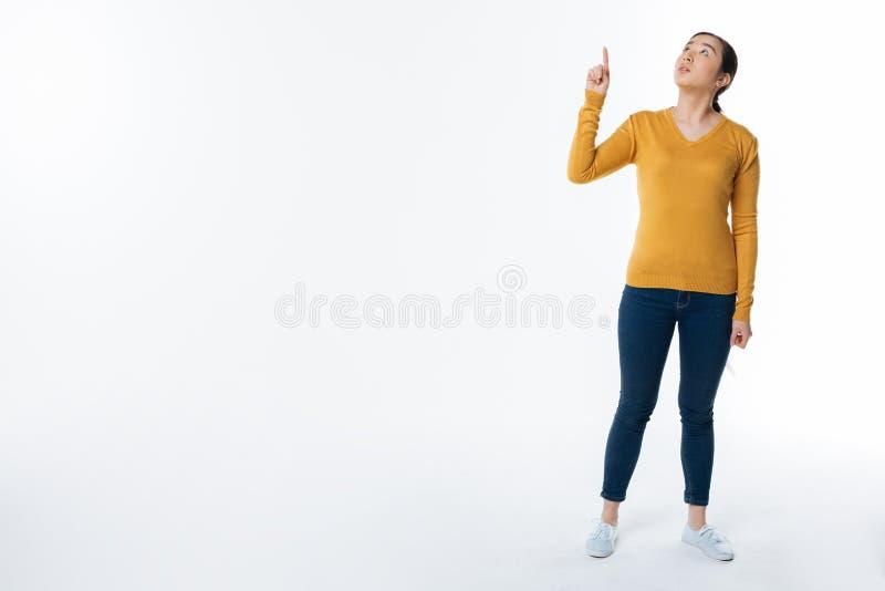 Ernste junge Frau, die gegen weißen Hintergrund steht lizenzfreies stockbild