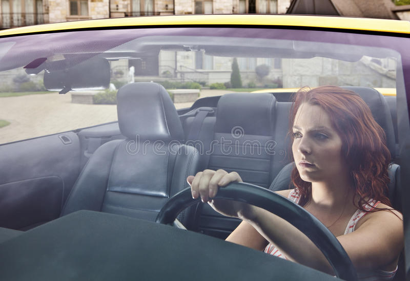 Ernste junge Frau, die weg von Haus antreibt lizenzfreie stockfotografie