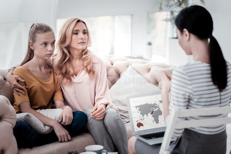 Ernste Mutter und ihre Tochter, die an Psychologen teilnimmt stockbild