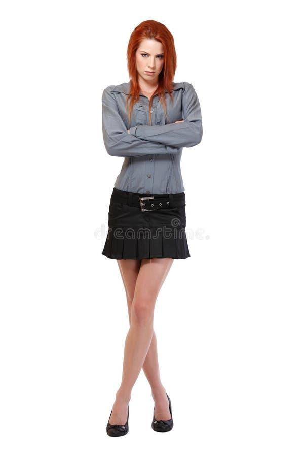 Ernste Redheadfrau, die auf weißem Hintergrund aufwirft lizenzfreie stockfotos