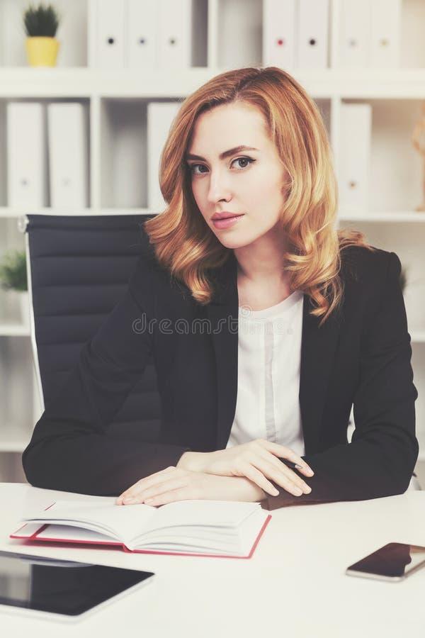 Ernste rote behaarte Geschäftsfrau mit Notizbuch lizenzfreie stockfotografie