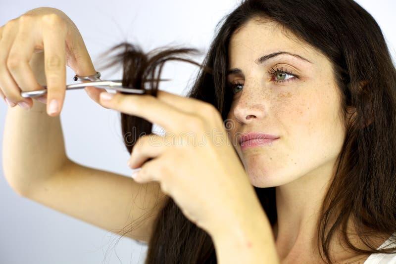 Ernste schöne Frau, die Haar der aufgeteilten Enden schneidet stockfotos