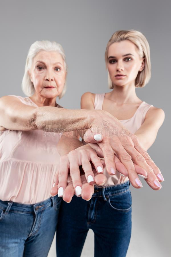 Ernste schöne Frau, die ihre gekreuzten Finger mit Maniküre zeigt lizenzfreies stockfoto