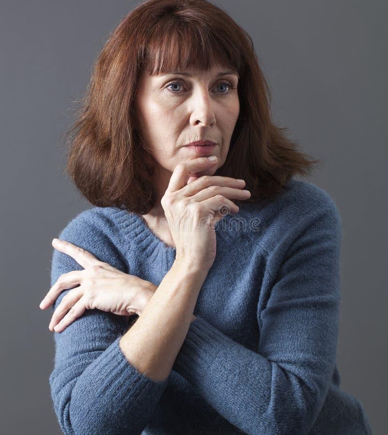 Ernste schöne Frau 50s, die nachdenklich schaut lizenzfreie stockbilder