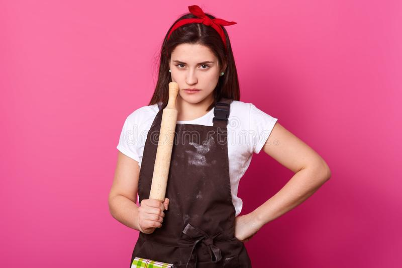 Ernste schlanke Frau hält backendes Nudelholz, trägt das braune Schutzblech, das mit Mehl, weißem T-Shirt und rotem Stirnband ges stockfotos