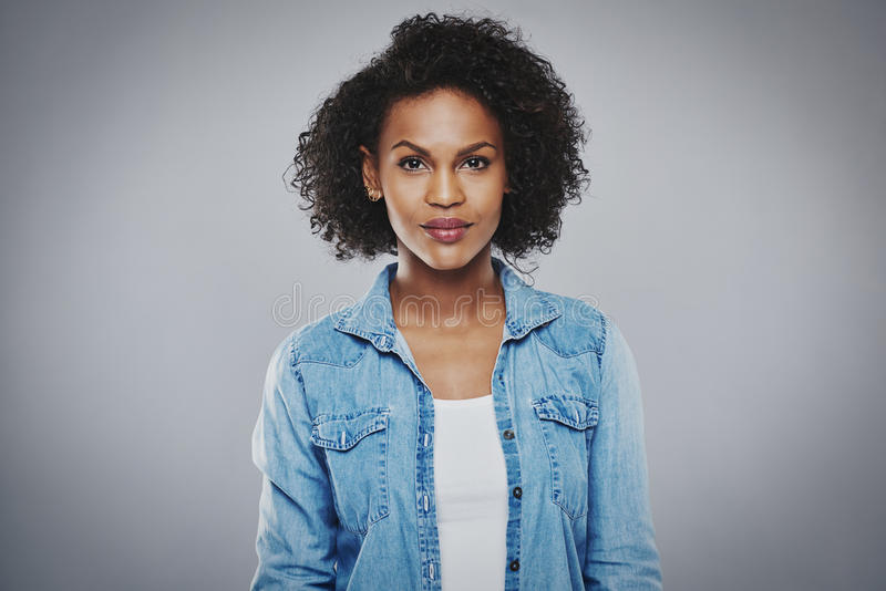 Ernste schwarze Frau mit blauem Baumwollstoffhemd stockbild