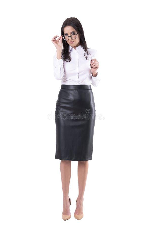Ernste sexy Geschäftsfrau oder Lehrer, welche die Augengläser betrachten Kamera justiert oder aufträgt lizenzfreie stockbilder