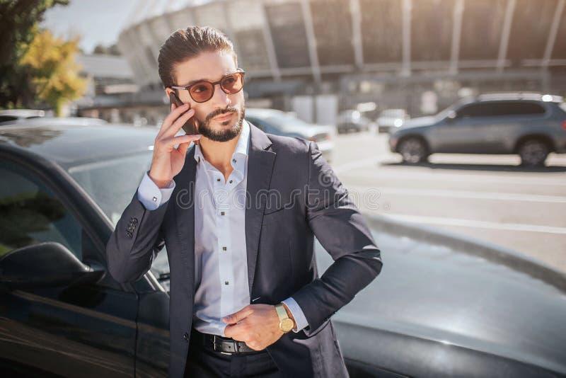 Ernste und starke junge Geschäftsmannstände am Auto und Gespräche am Telefon Er trägt Sonnenbrille Kerl schaut, um zu berichtigen lizenzfreie stockfotografie