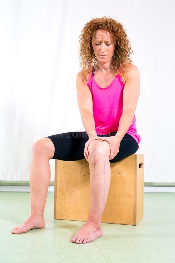 Ernste verletztes Bein der Frau Holding lizenzfreie stockfotos