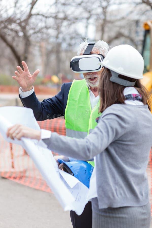 Ernster älterer Architekt oder Geschäftsmann, der Schutzbrillen der virtuellen Realität verwendet, um Bauvorhaben auf einer Baust stockfotografie