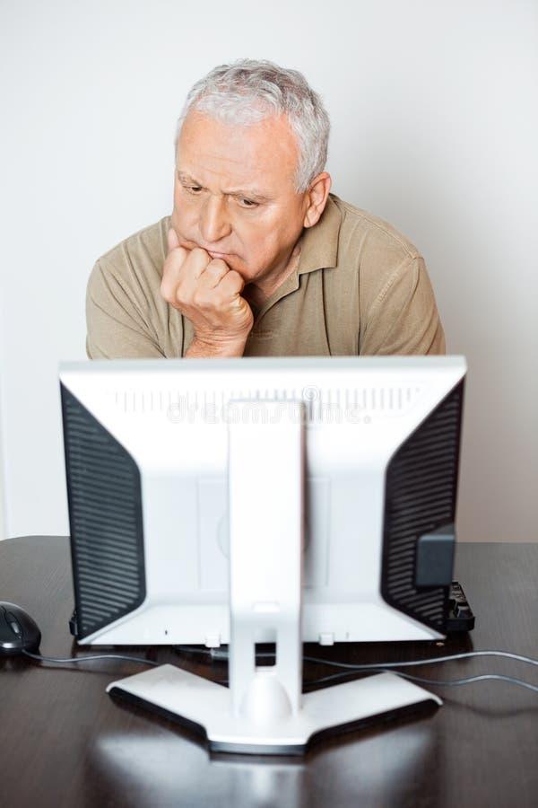 Ernster älterer Mann, der Computer-Monitor in der Klasse betrachtet stockfotografie
