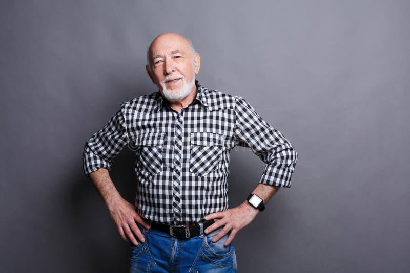 Ernster älterer Mann, der mit den Händen auf Hüften aufwirft stockfotos