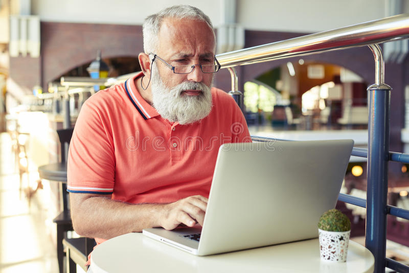 Ernster älterer Mann, der mit Laptop arbeitet stockfoto