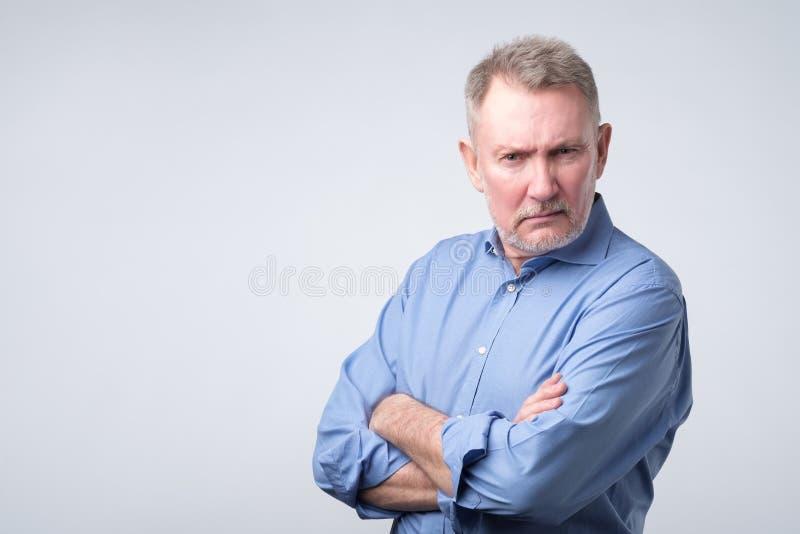 Ernster älterer Mann im blauen Hemd mit den gefalteten Armen stockfoto