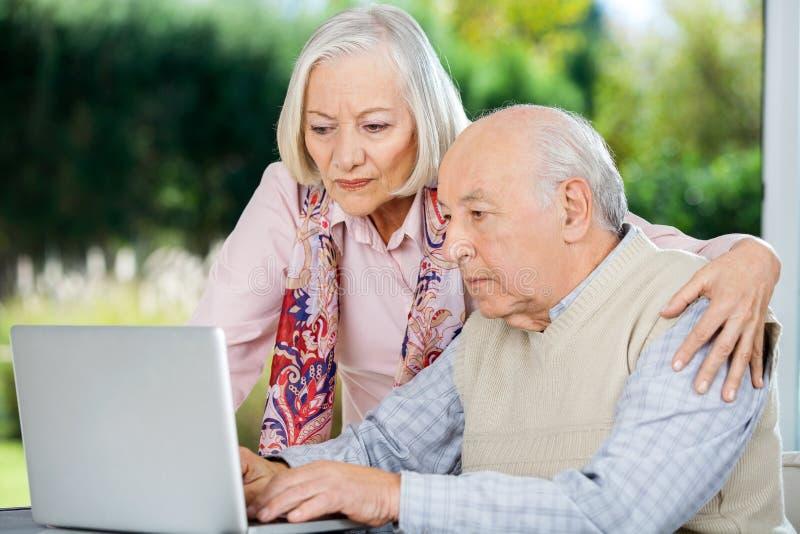 Ernster älterer Mann und Frau, die Laptop verwendet stockbilder