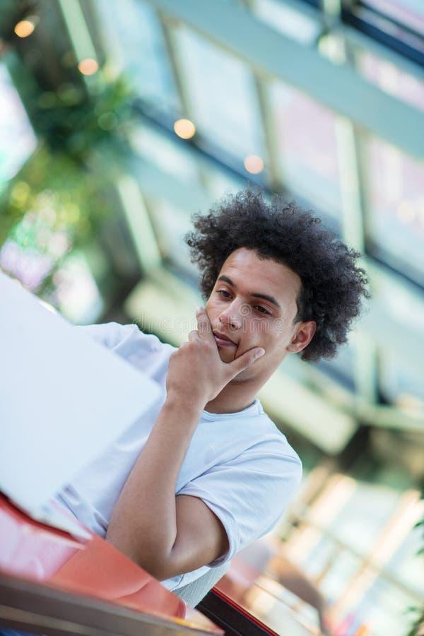 Ernster afroer-amerikanisch m?nnlicher Student im T-Shirt, das an der Cafeteria den Mitnehmerkaffee trinkend arbeitet an seiner P lizenzfreies stockfoto