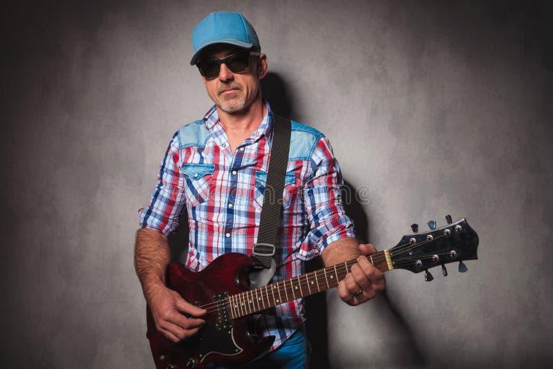Ernster alter Gitarrist, der seine E-Gitarre spielt lizenzfreies stockbild