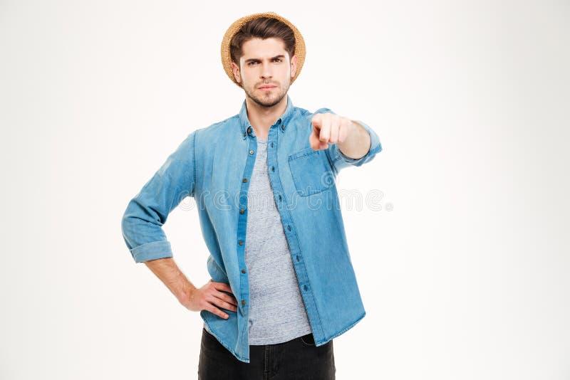 Ernster attraktiver junger Mann, der auf Kamera steht und zeigt stockfotos