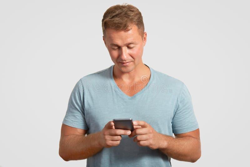 Ernster attraktiver Mann hält modernes intelligentes Telefon, Textmitteilungen, Kontrollen sein E-Mail-Kasten, angeschlossen an d stockfoto