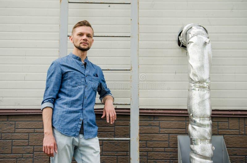 Ernster bärtiger junger Mann im Denimhemd steht nahe der Wand des Industriegebäudes nahe Leiter und betrachtet direkt  stockbild