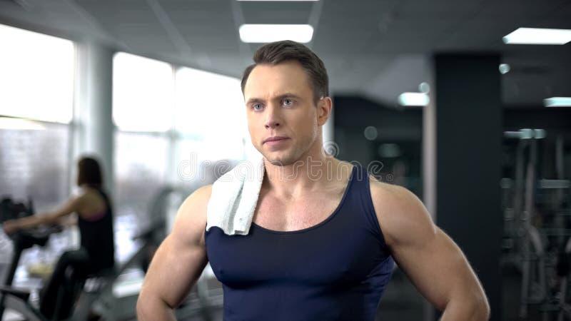 Ernster Bodybuilder mit Tuch auf der Schulter, die nach hartem Training in der Turnhalle sich entspannt stockbild