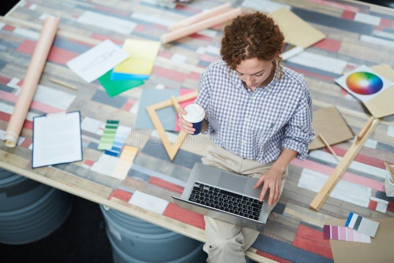 Ernster Damendesigner, der Laptop im kreativen Studio verwendet lizenzfreie stockbilder