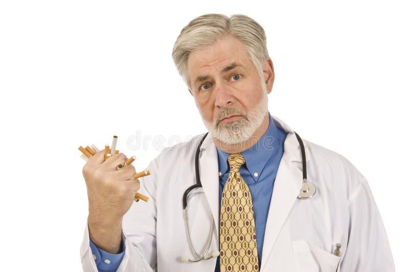 Ernster Doktor Crushing Cigarettes lizenzfreie stockfotografie