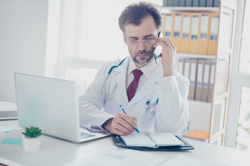 Ernster Doktor konsultiert Patienten durch das Telefon und schreibend tun Sie lizenzfreies stockfoto