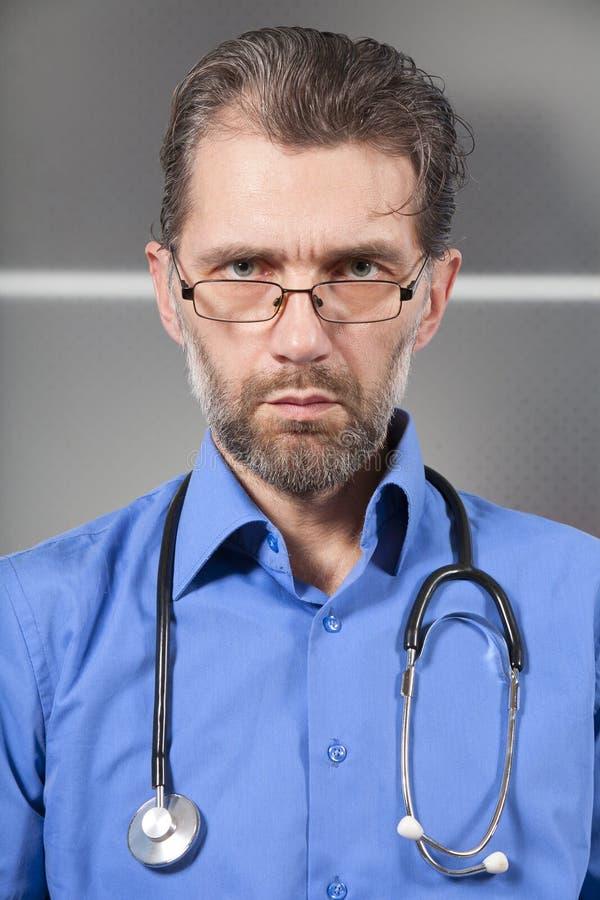 Ernster Doktor mit einem Stethoskop lizenzfreies stockbild
