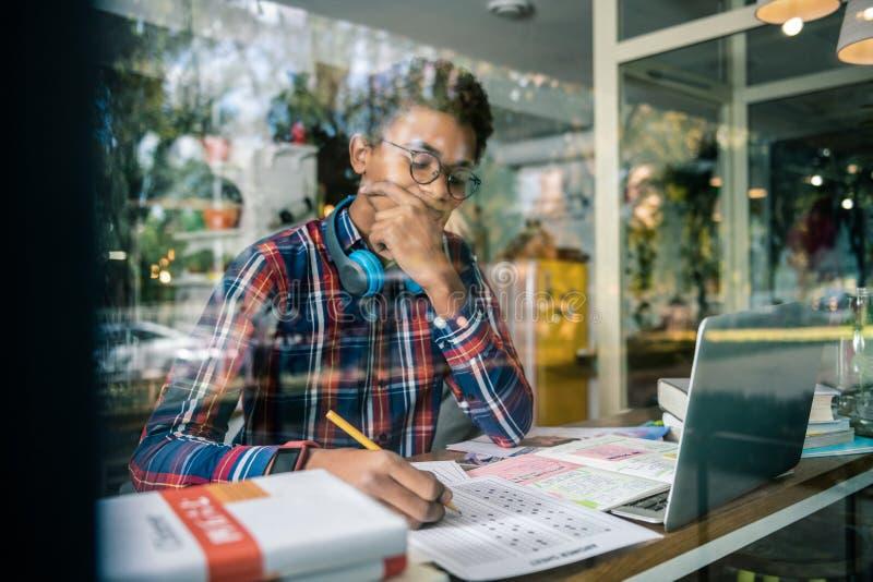Ernster durchdachter Student, der auf seine Aufgabe sich konzentriert stockfotografie