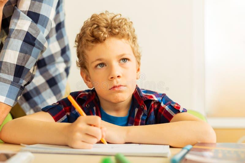 Ernster gebohrter blonder Junge, der seine Aufgabe schreibt lizenzfreie stockfotografie