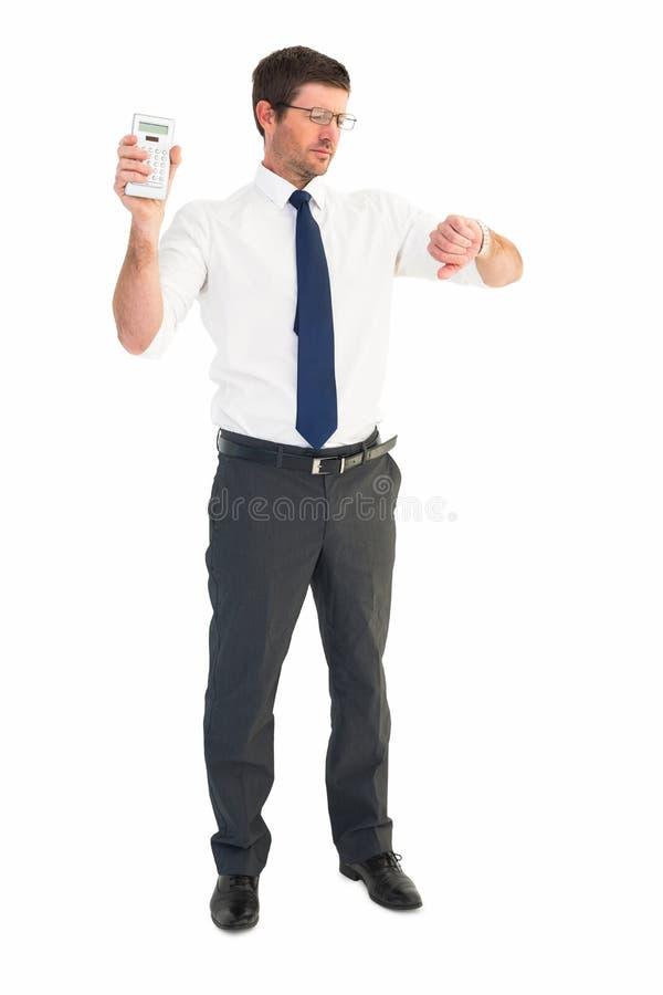 Ernster Geschäftsmann, der den Taschenrechner überprüft Zeit hält stockbilder