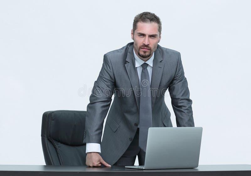 Ernster Geschäftsmann, der hinter einem Schreibtisch steht Lokalisiert auf Weiß lizenzfreie stockfotos