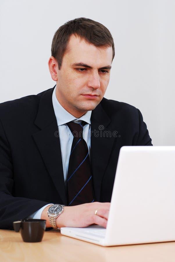Ernster Geschäftsmann, der an Laptop arbeitet stockfotos