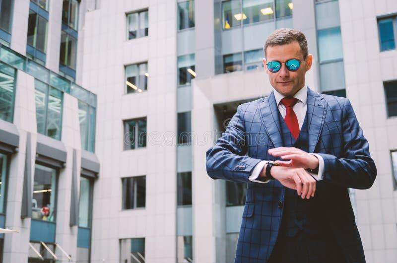 Ernsthafter Geschäftsmann in einem modischen, stylischen Schachanzug auf dem Hintergrund eines beton-grauen Geschäftszentrums lizenzfreie stockfotos